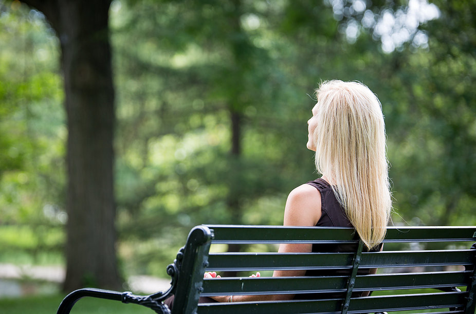 Back view of woman sitting on park bench.